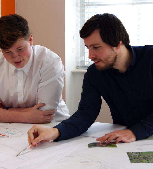 A man pointing towards a drawing off a sitemap, while another man watches intently.